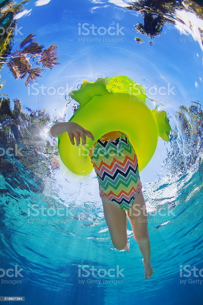 Child swimming on yellow inflatable tube in pool stock photo