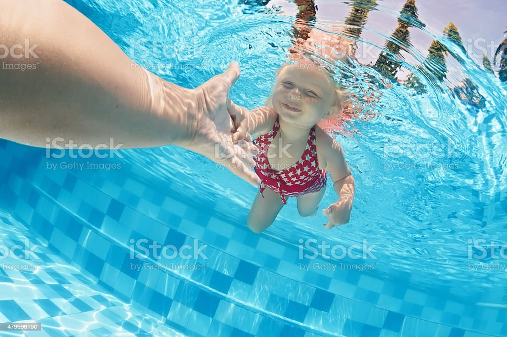 Child swimming underwater in the pool with parents stock photo