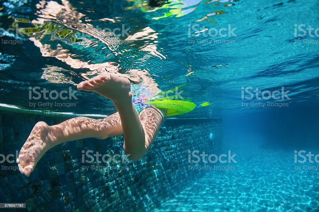 Child swimming with fun on yellow ring in blue pool stock photo