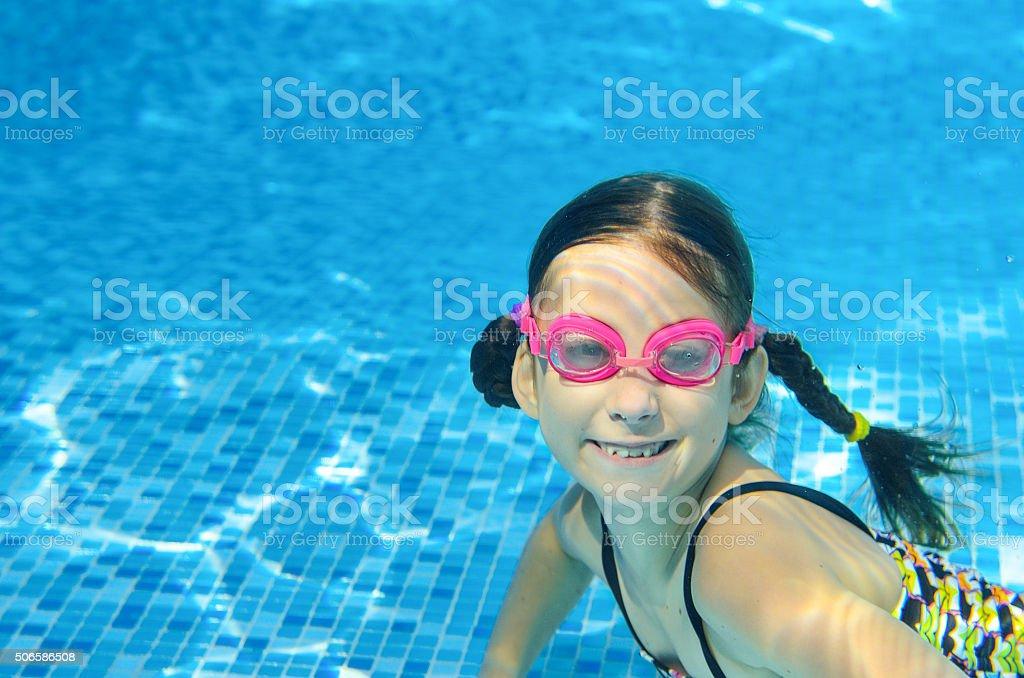 Child swims in pool underwater, girl has fun under water stock photo