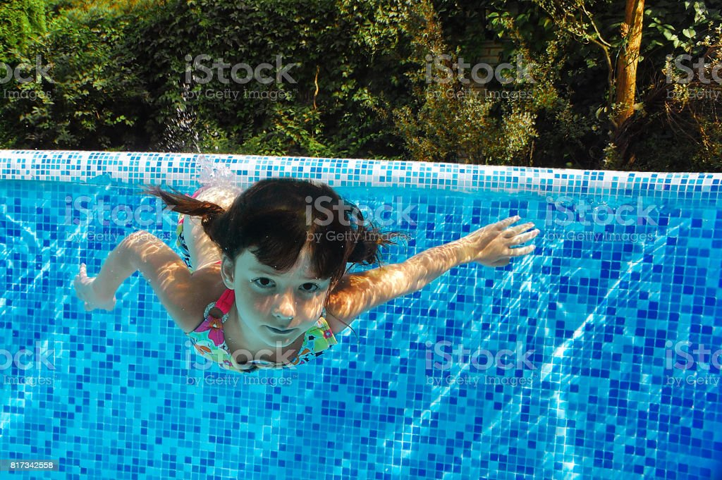 Child swims in pool underwater, happy active girl dives and has fun under water, kid fitness and sport on family vacation stock photo
