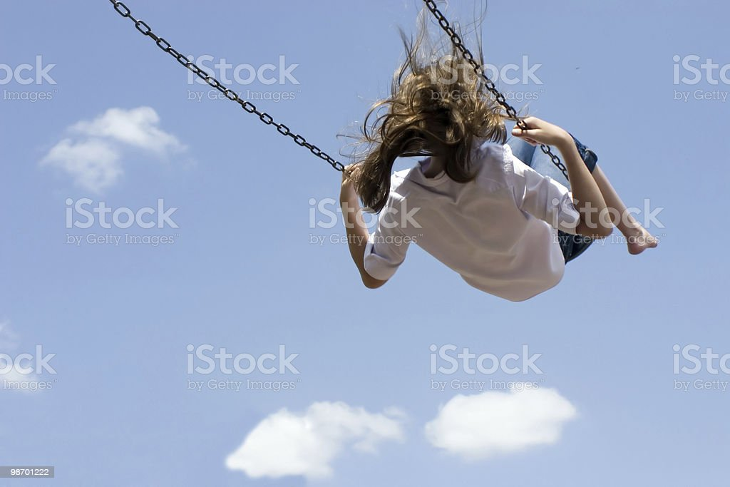 Child swinging high against blue sky stock photo