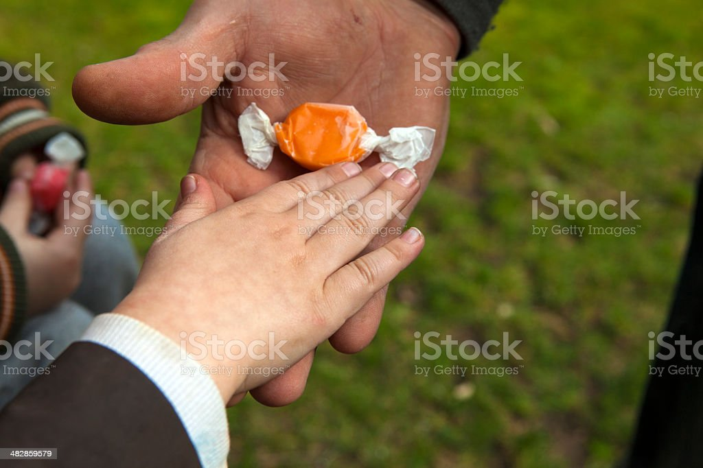 Child taking candy from an adult stock photo