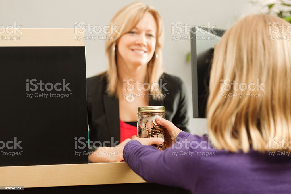 Child Taking Her Coin Jar of Savings to Bank Teller stock photo