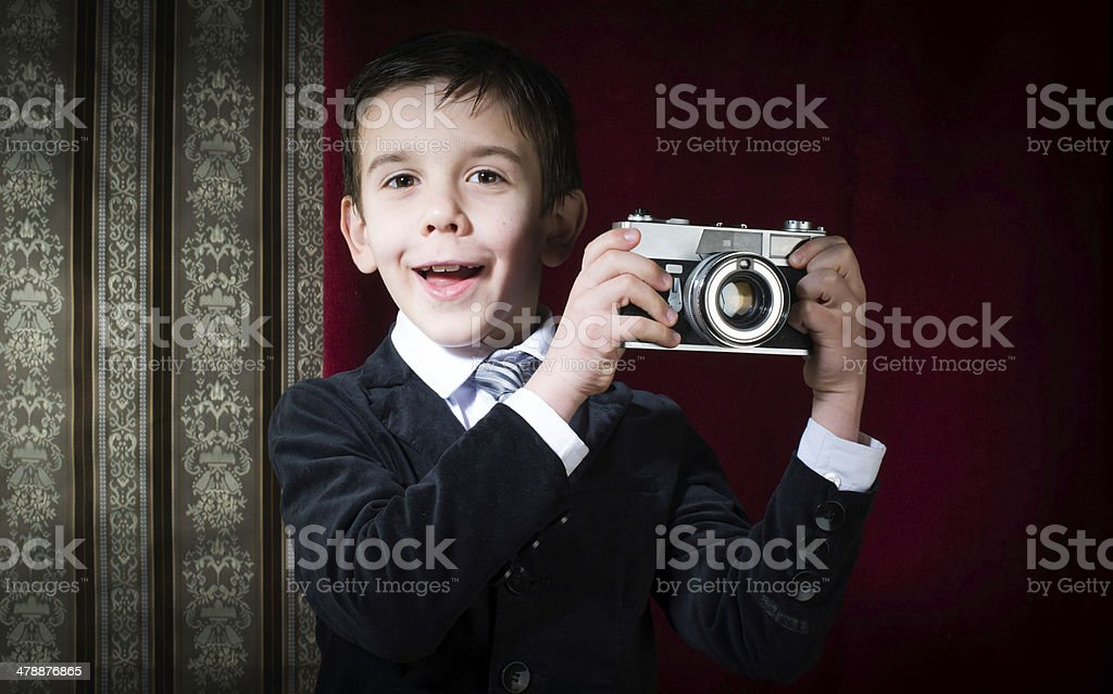 Child taking pictures with vintage camera stock photo