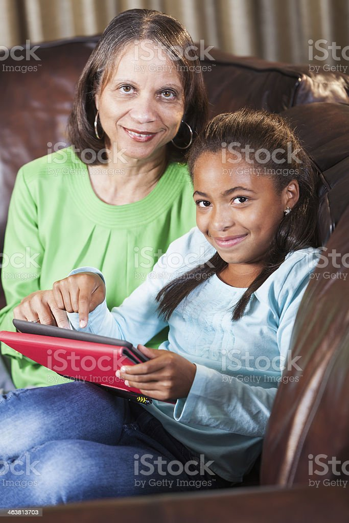 Child teaching grandparent how to use digital tablet stock photo