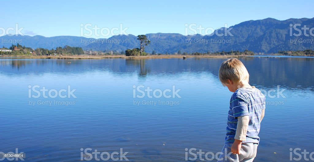 Child throws stones into Water stock photo