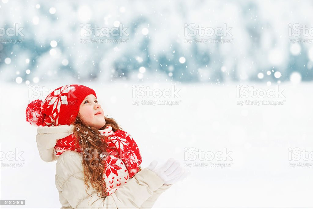 Child to catch falling snowflakes. stock photo