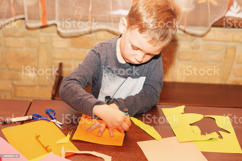 Child trace around a hand on paper with crayons stock photo