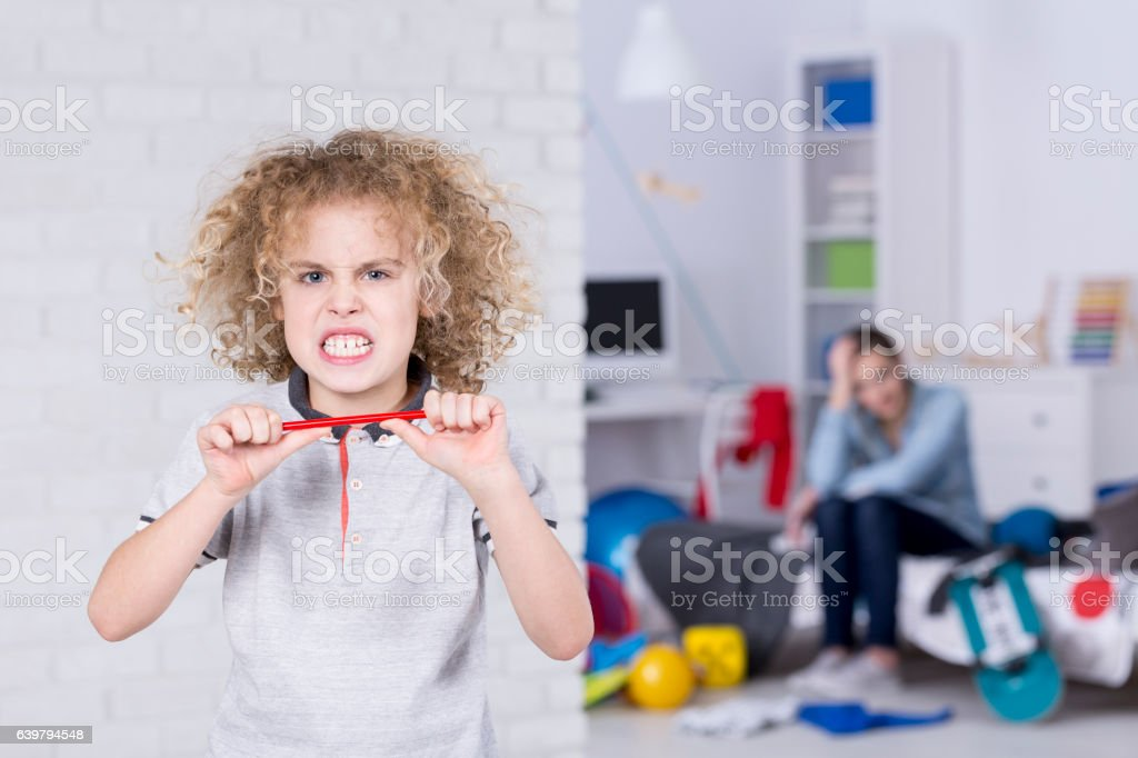 Child trying to break pencil stock photo