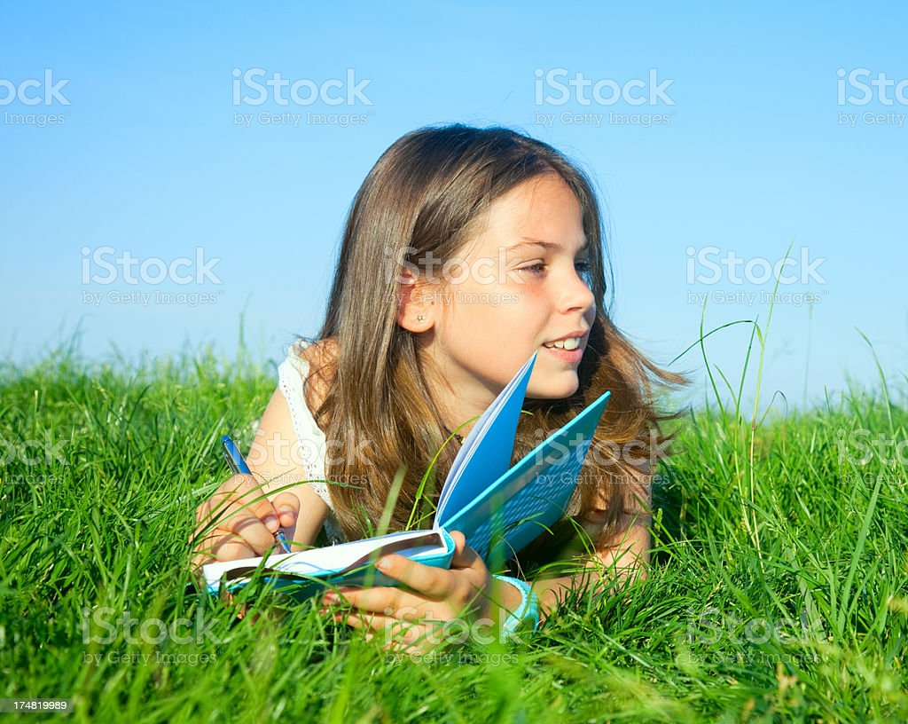 Child twriting diary outdoors royalty-free stock photo