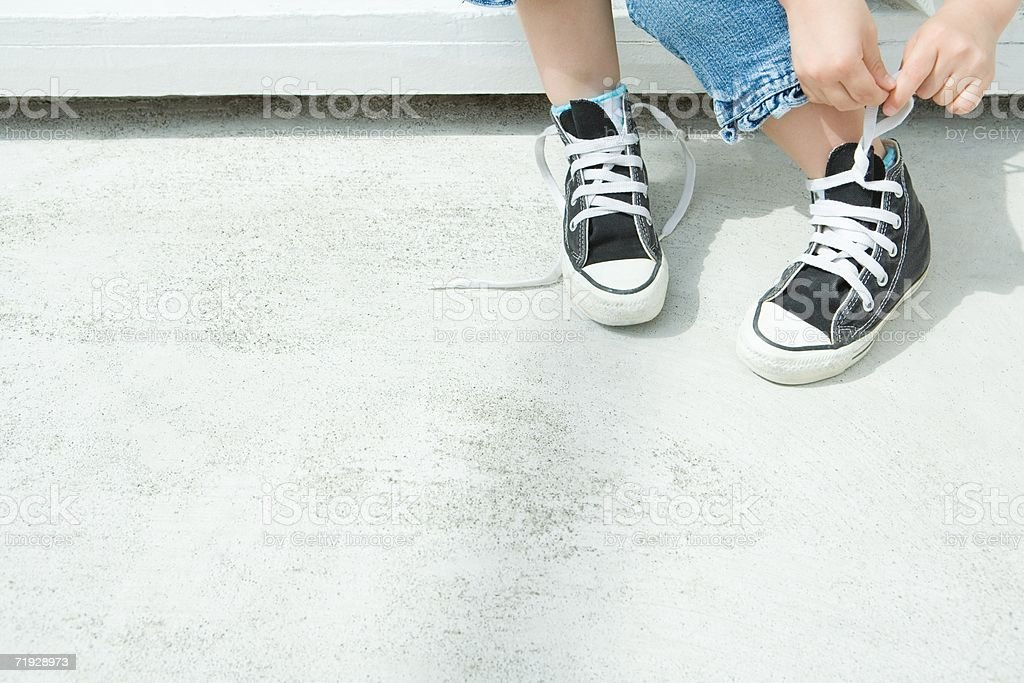 Child tying their shoelaces royalty-free stock photo