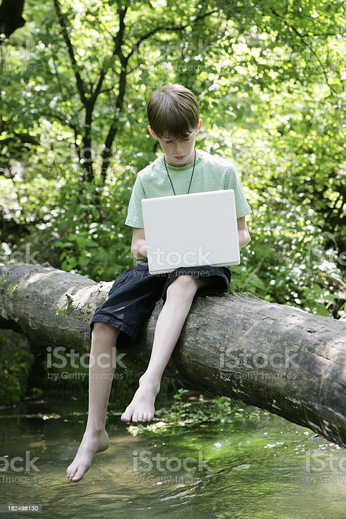Child Uses Computer in Nature- Pointing and Learning royalty-free stock photo
