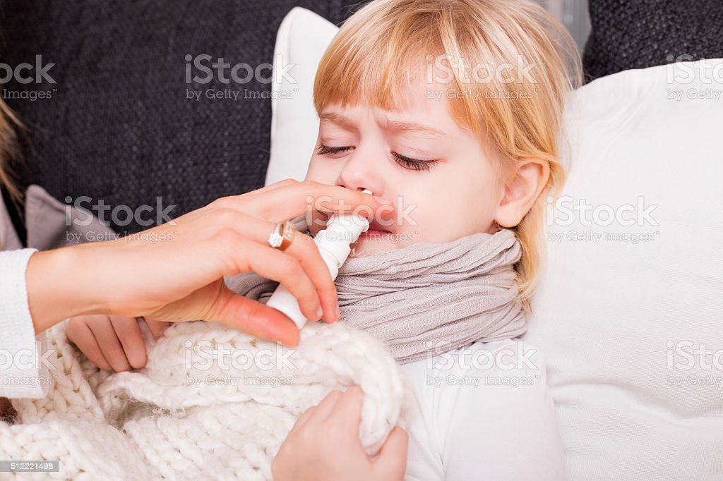 Child using medicine to treat cold stock photo