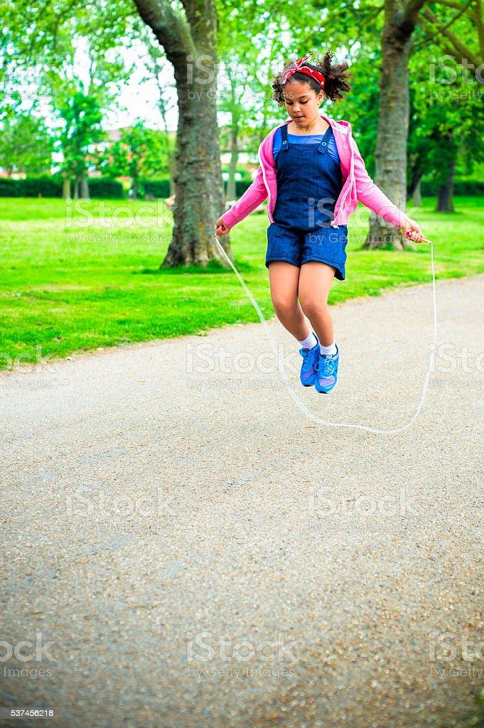 Child (9 -10) Using Skipping Rope in playground stock photo