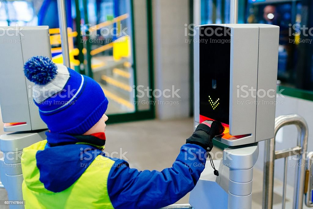 Child validating a ticket in railway or underground entrance. stock photo