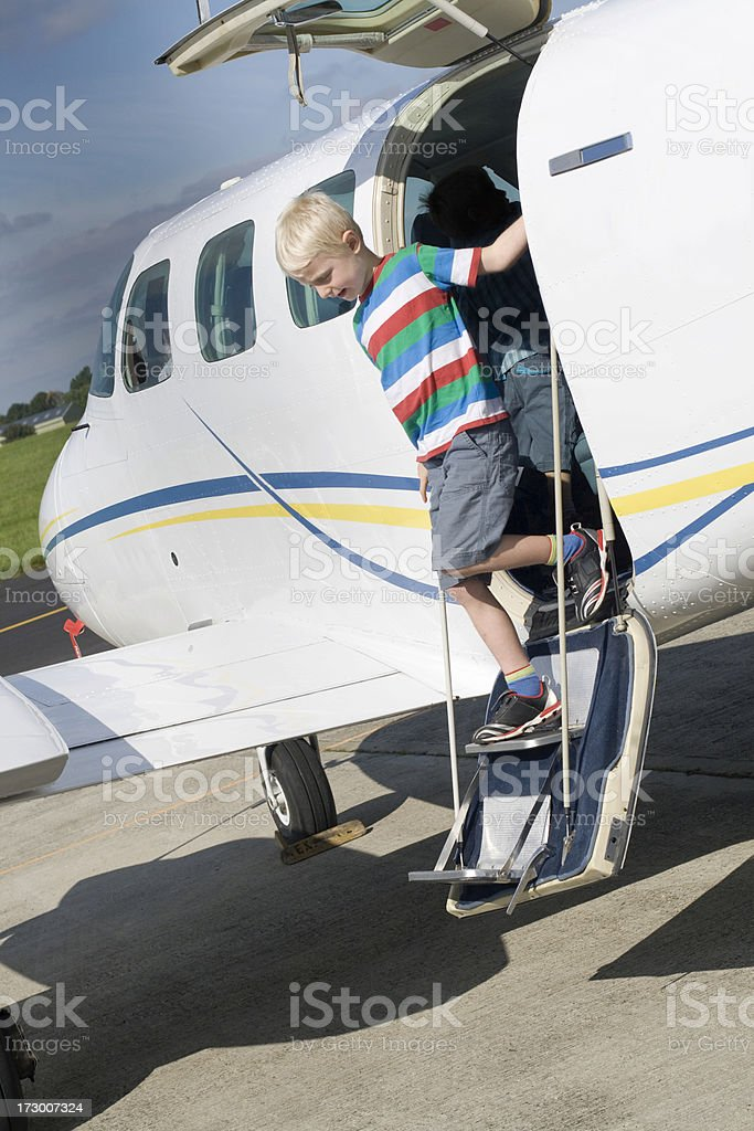 Child walking down the steps of a light aircraft stock photo