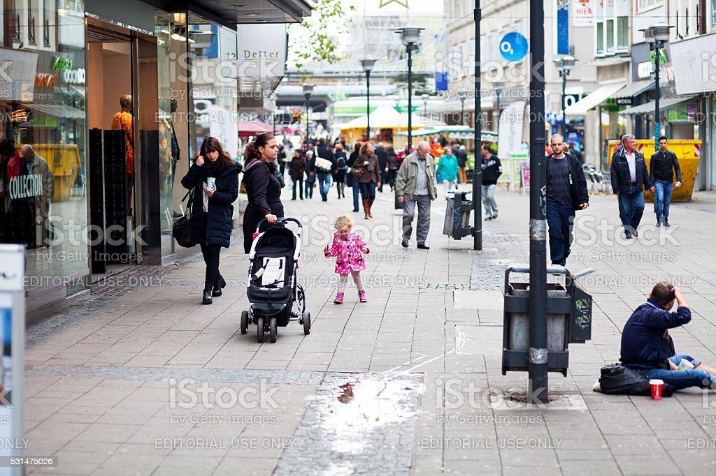 Child walking in pedestrian zone between people stock photo