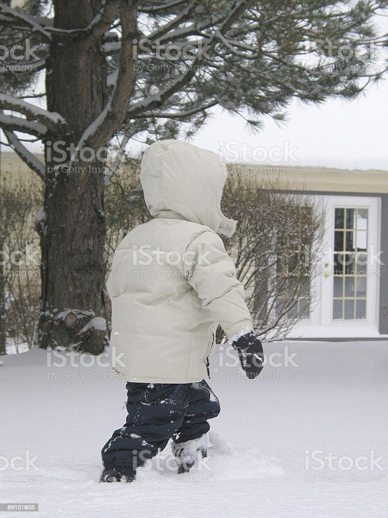 Child walking in the snow stock photo
