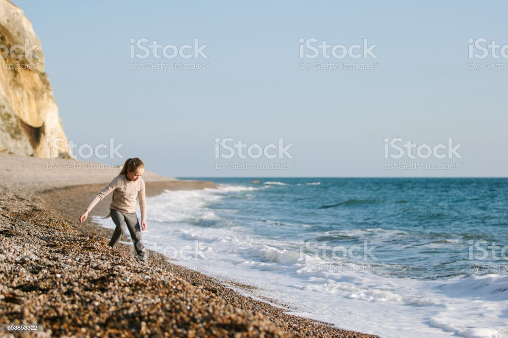 Child walking on a beach stock photo