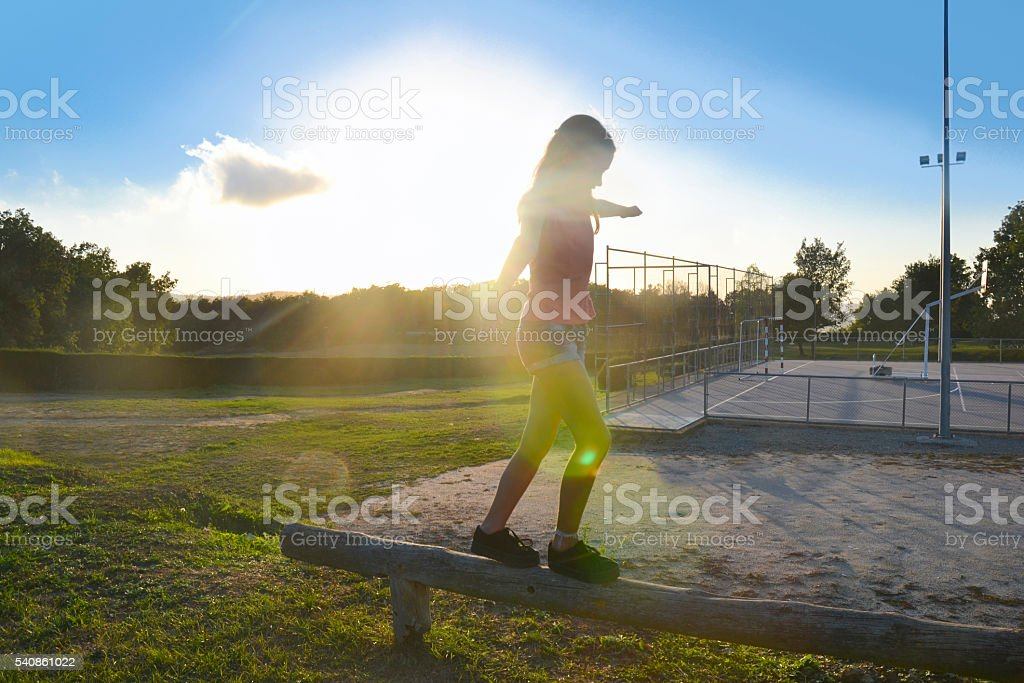 Child walking on a fence stock photo
