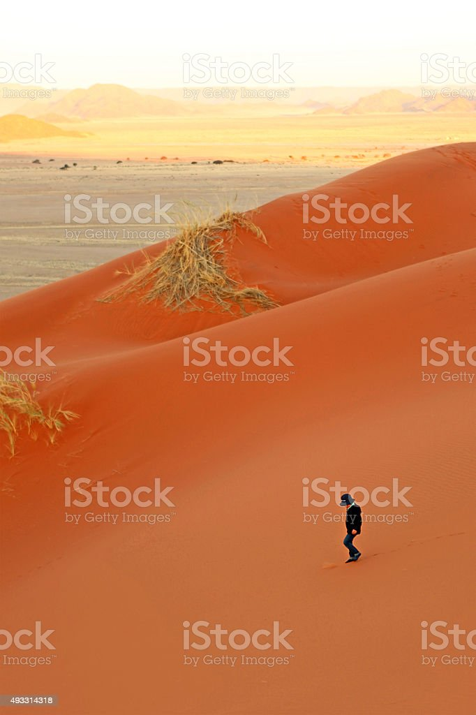 Child Walking on Red Sand Dunes in Sossusvlei Namibia stock photo