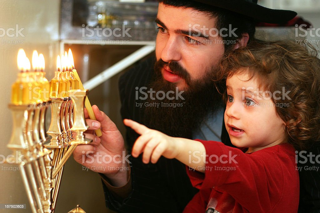 Child watching Father Lighting the Menorah stock photo