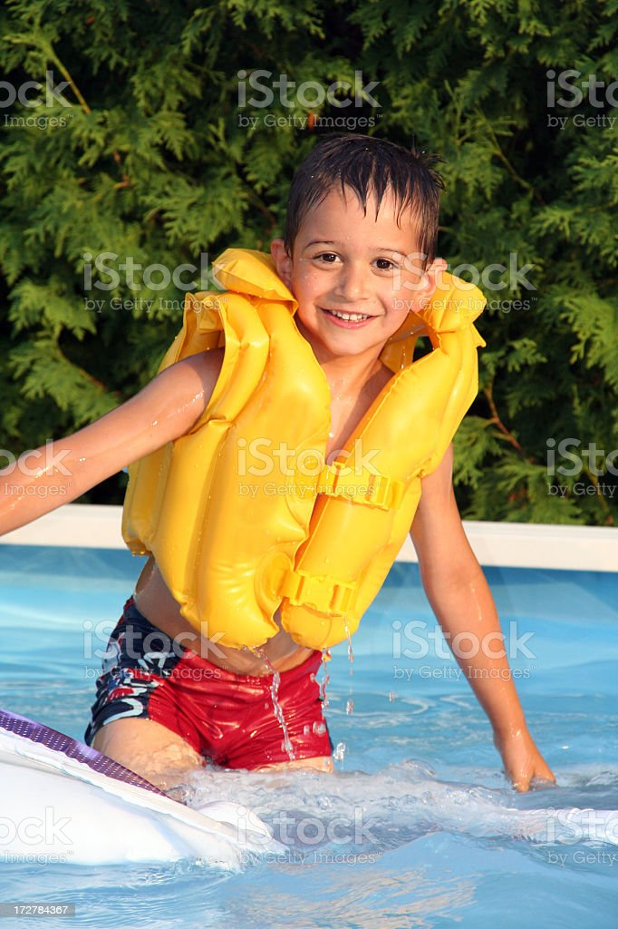 Child Wearing a Yellow Life Jacket in Swimming Pool royalty-free stock photo