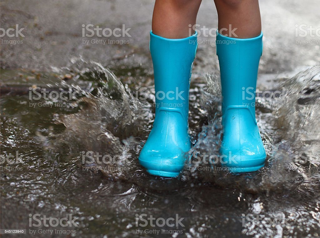 Child wearing blue rain boots jumping into a puddle stock photo