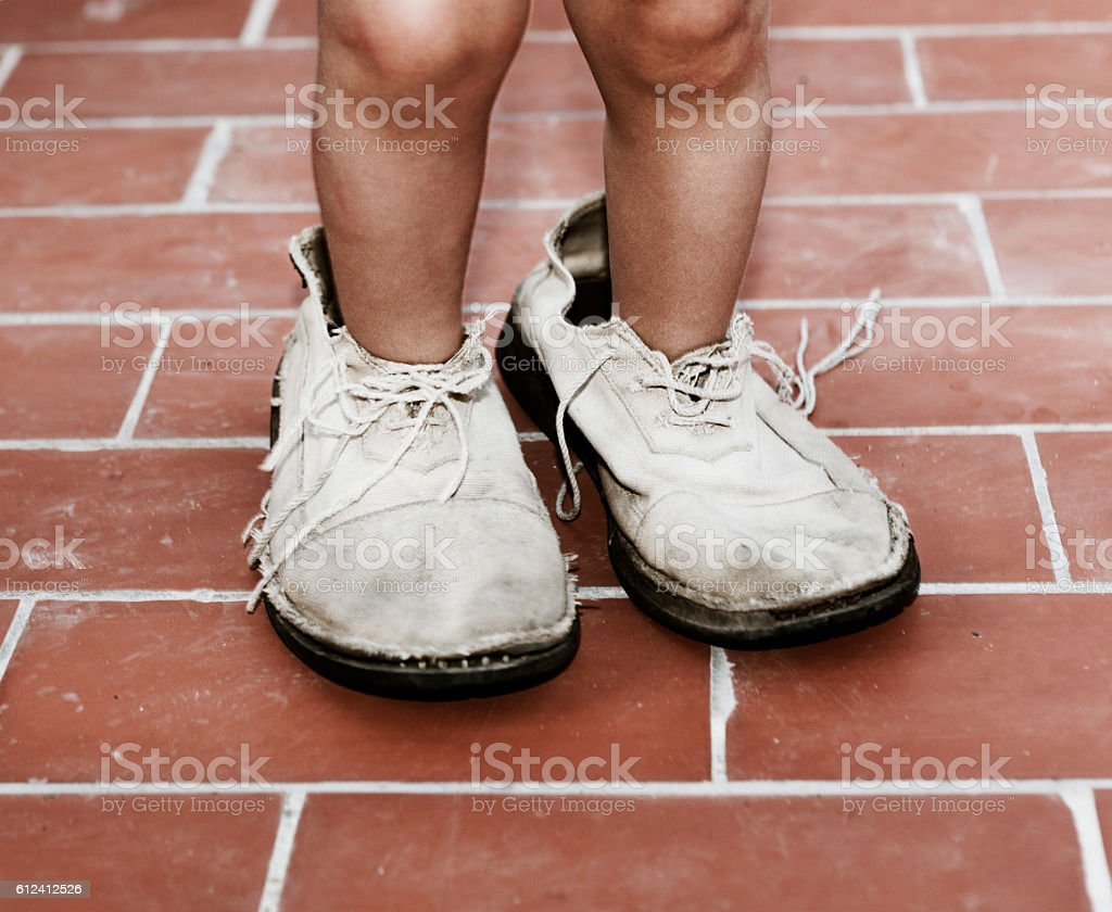 Child wearing deteriorated adult shoes stock photo