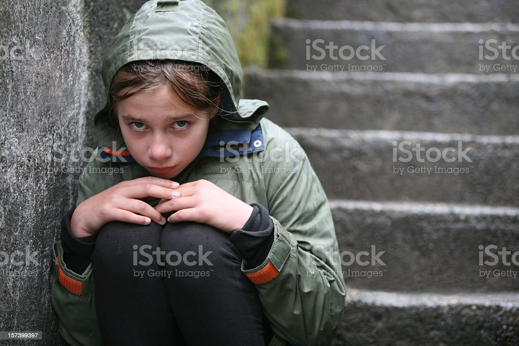 Child wearing green coat sitting on stairs stock photo