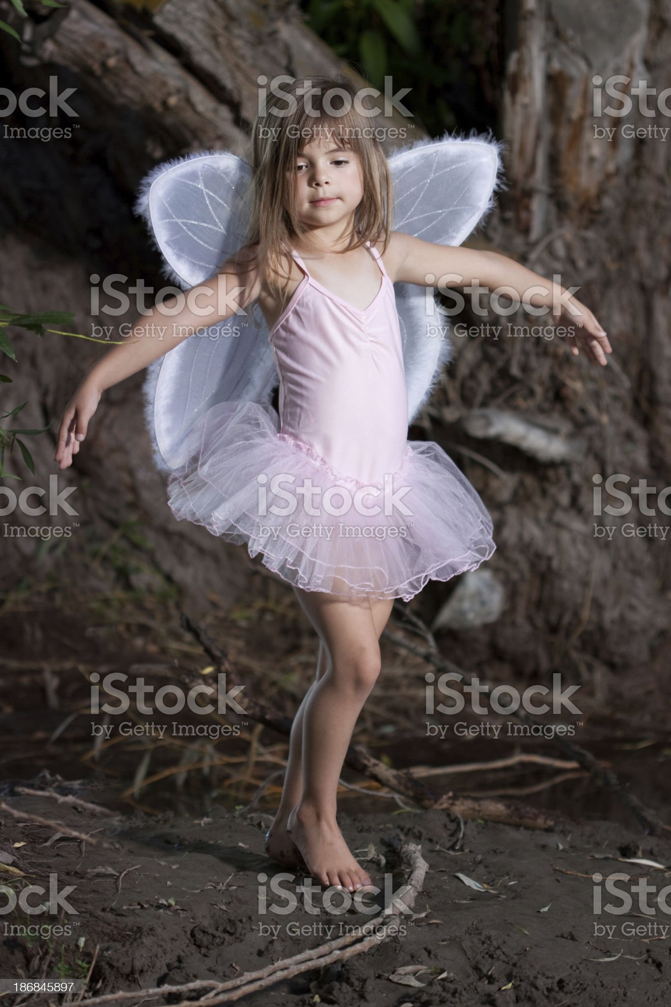 Child Wearing Wings Dancing in Forest royalty-free stock photo