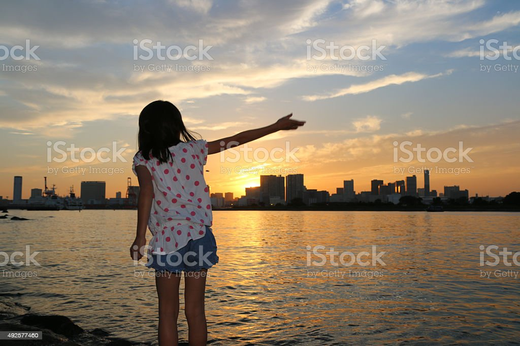 Child who throws a stone towards the sunset stock photo