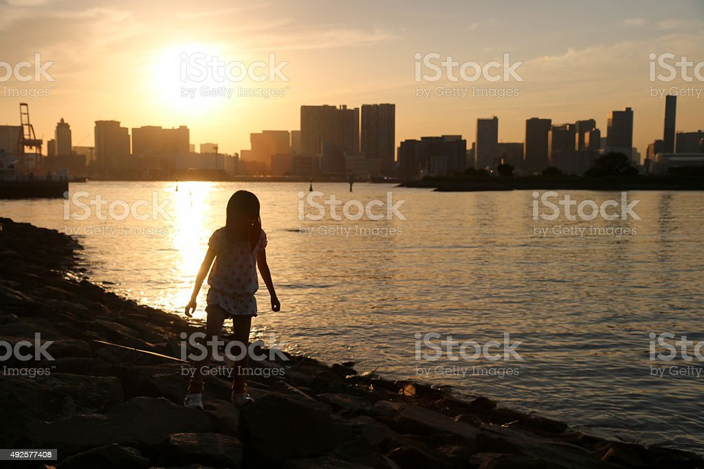 Child who walks the shore lighted up stock photo