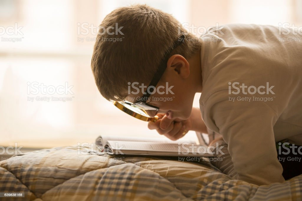 Child with a magnifying glass course stock photo