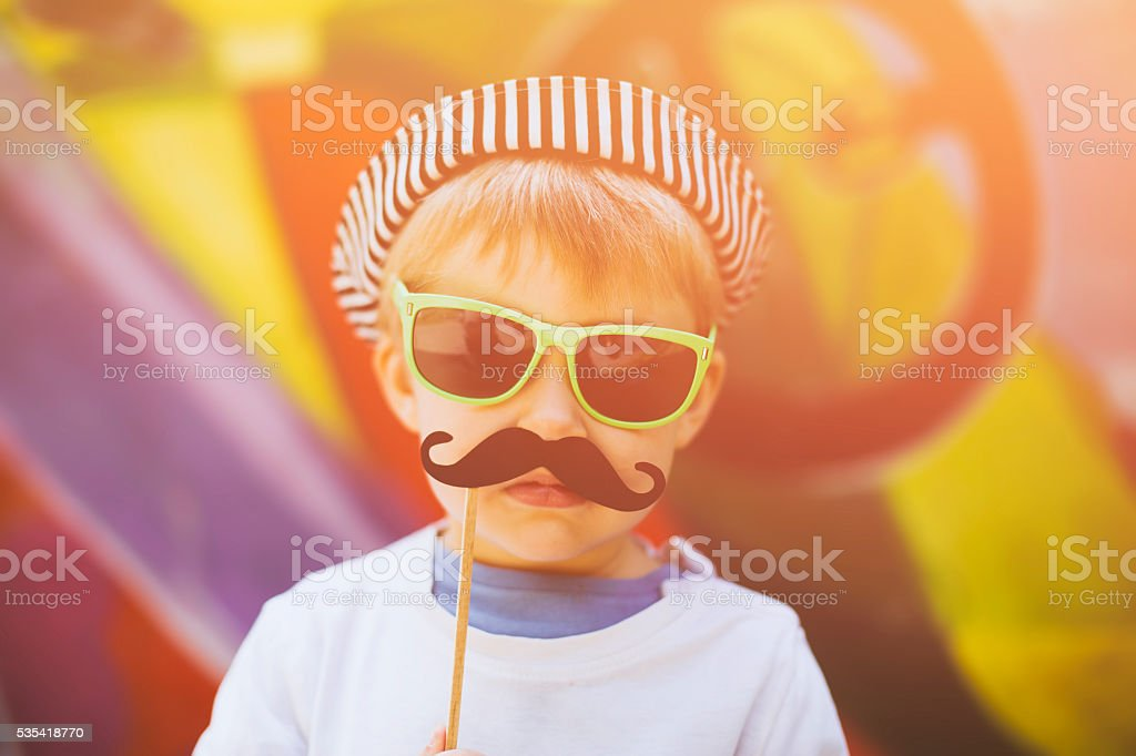Child with a mustache on a stick stock photo