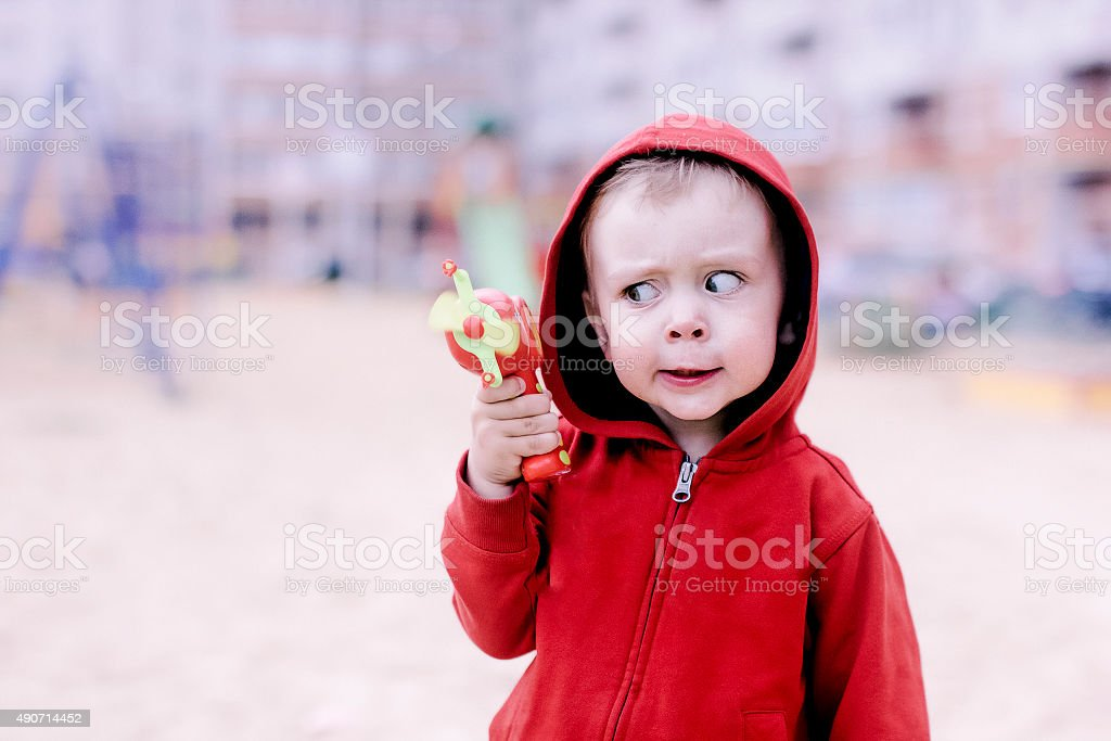 child with a toy gun stock photo