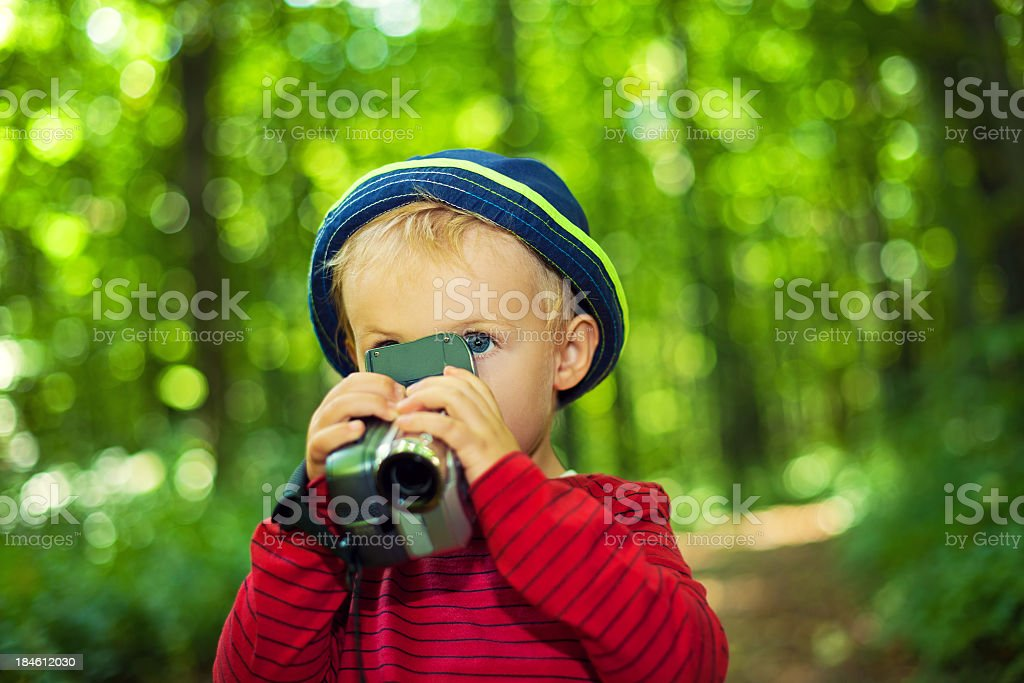 Child with a video camera in the forest royalty-free stock photo