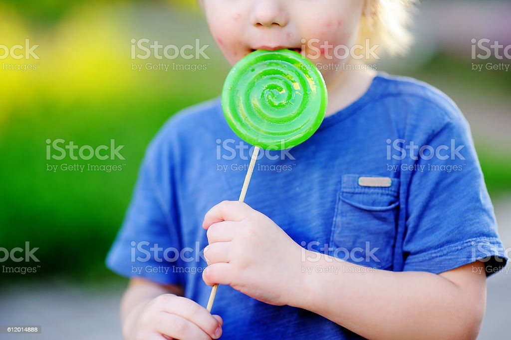 Child with allergic reaction eating big green lollipop stock photo