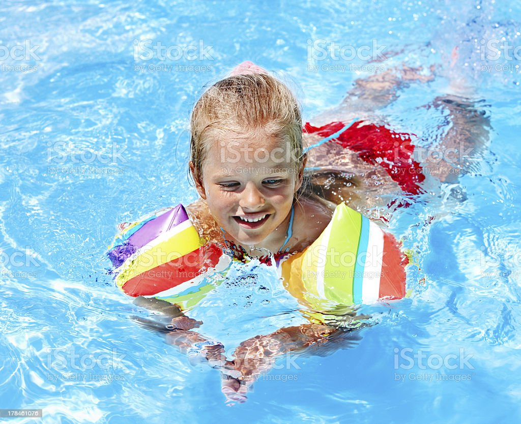 Child with armbands in swimming pool. stock photo