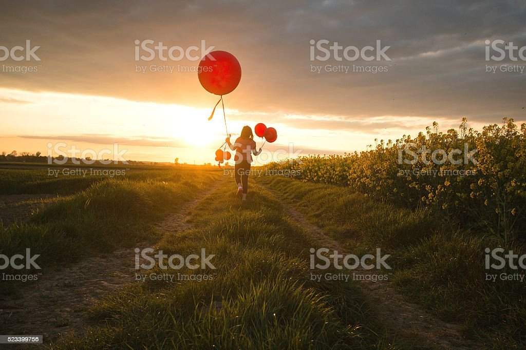 Child with balloons running on the country road stock photo