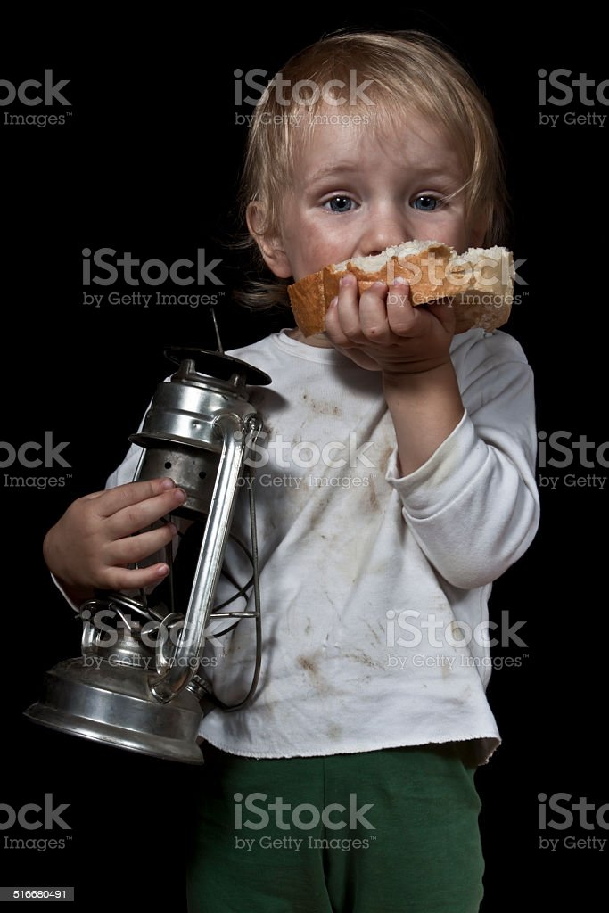 child with bread and oil lamp stock photo