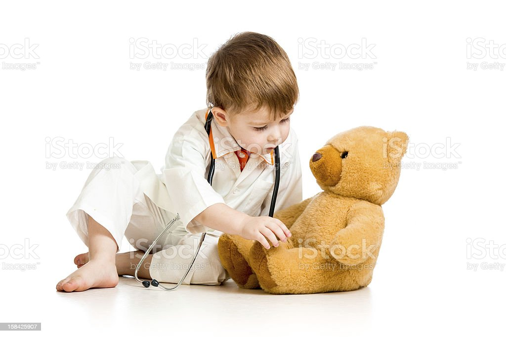 child with clothes of doctor and teddy bear over white stock photo