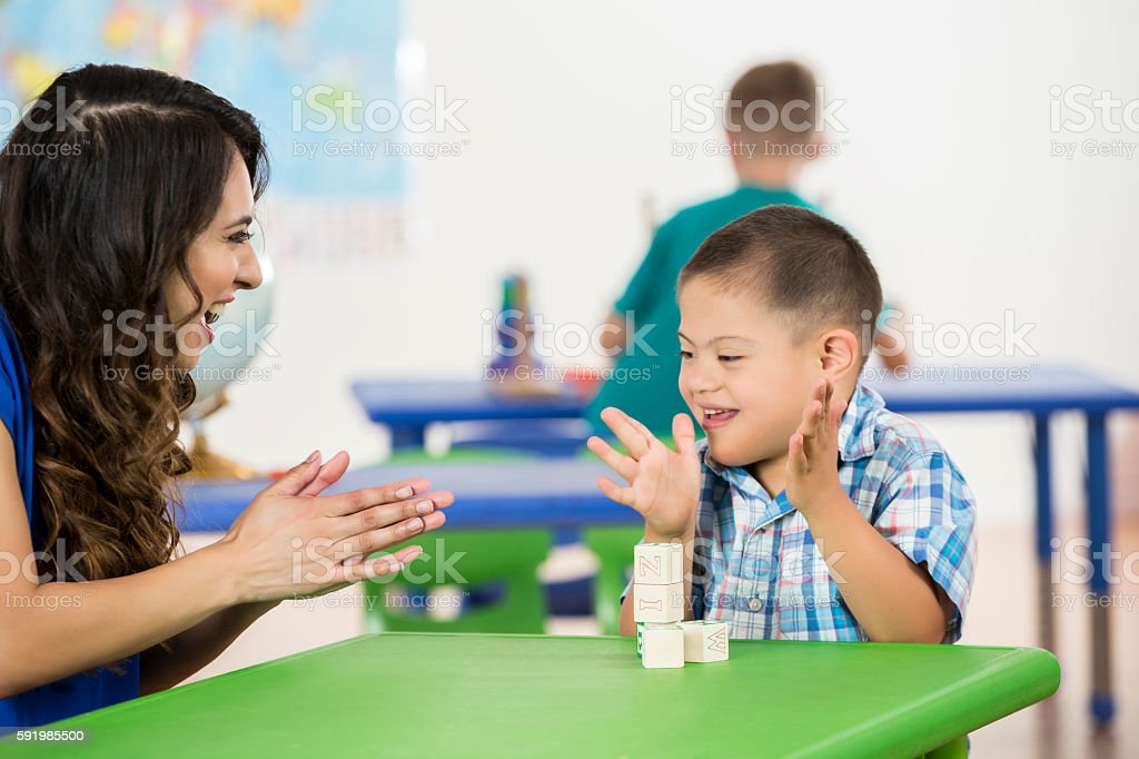 Child with Down Syndrome clapping, playing with blocks in classroom stock photo