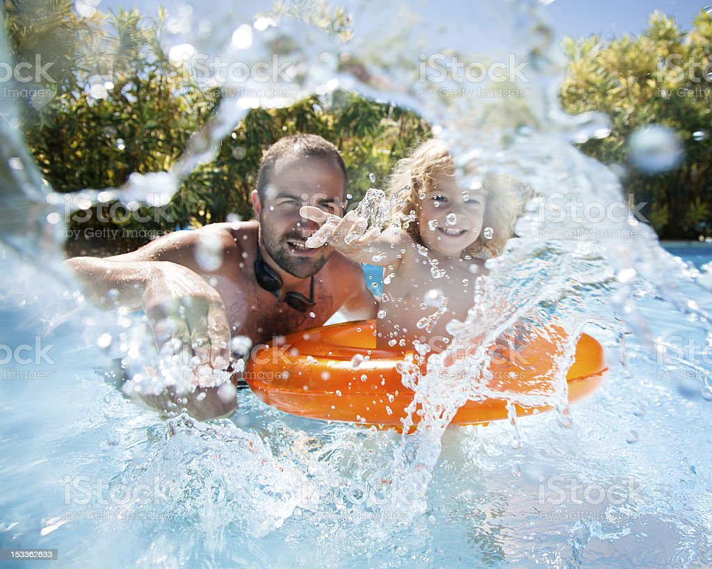 Child with father in swimming pool stock photo