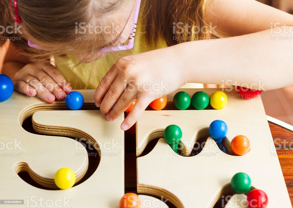 Child with glasses playing with pathfinder toy board stock photo