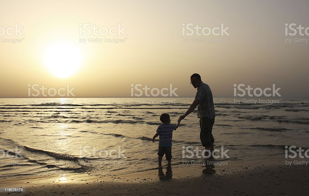 child with his father at sea. Sunset stock photo