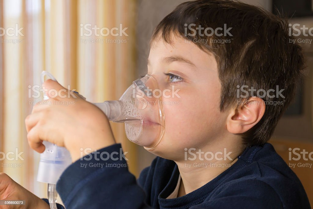 child with inhaler mask stock photo
