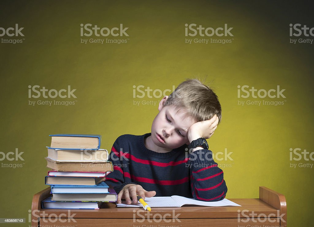 Child with learning difficulties. Tired boy doing homework. royalty-free stock photo