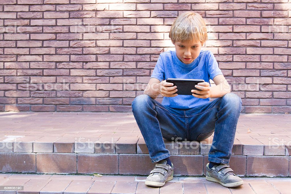 Child with mobile phone sitting outdoors. Boy looks at the stock photo